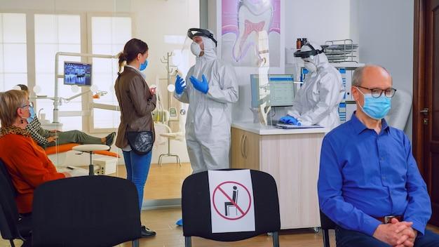 Medico con un discorso generale sul trattamento dei denti con il paziente in maschera di protezione in piedi nell'area di attesa, i pazienti che mantengono la distanza. concetto di nuova normale visita dal dentista nell'epidemia di coronavirus.
