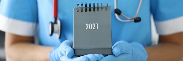 Il medico con il fonendoscopio al collo tiene il primo piano del calendario da tavolo in guanti di gomma