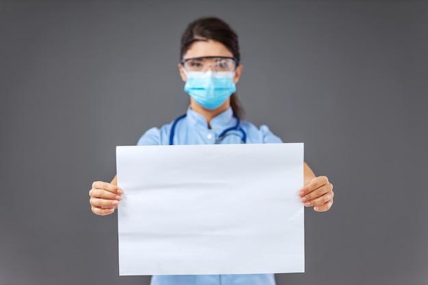 Medico con la maschera protettiva in piedi, tenendo la carta bianca e guardando la fotocamera.
