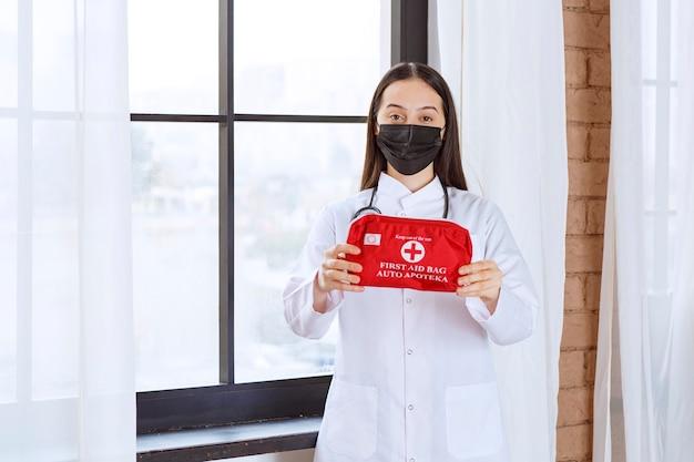 Medico con lo stetoscopio e la maschera nera che tiene un kit di pronto soccorso rosso.