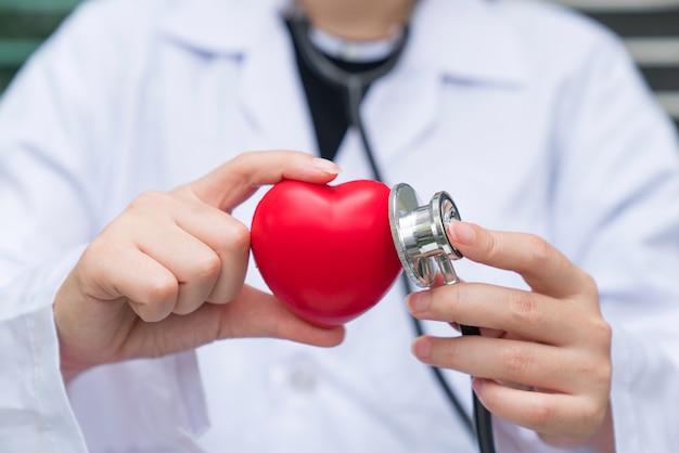 Un medico con stetoscopio esaminando il cuore rosso