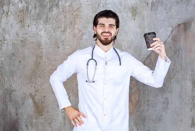 Medico con uno stetoscopio che tiene una tazza di bevanda nera usa e getta.