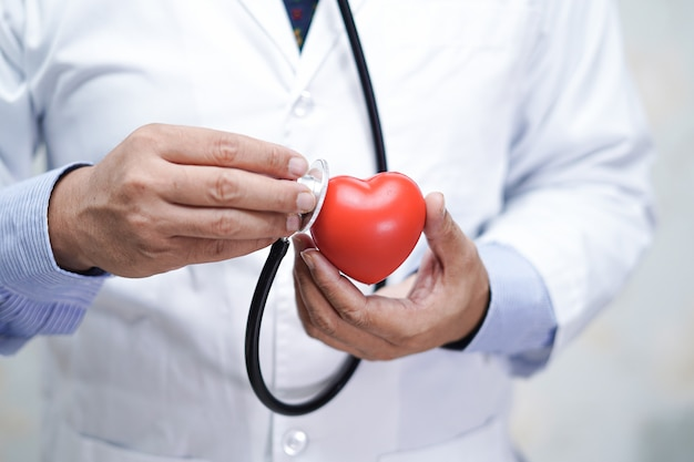 Medico con lo stetoscopio che tiene cuore rosso in mano