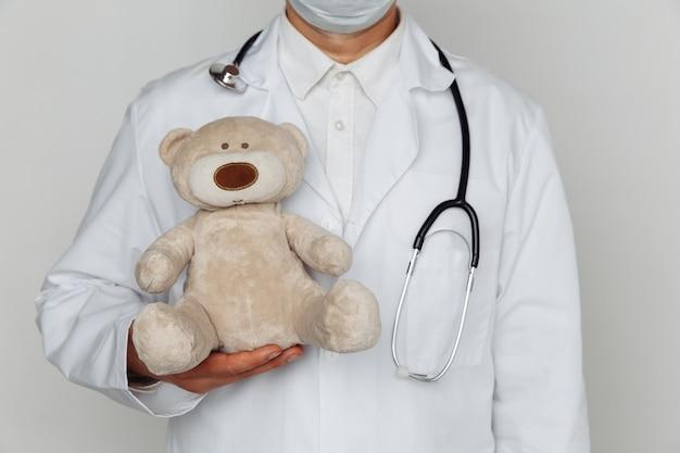 Medico con lo stetoscopio che tiene orsacchiotto in studio medico