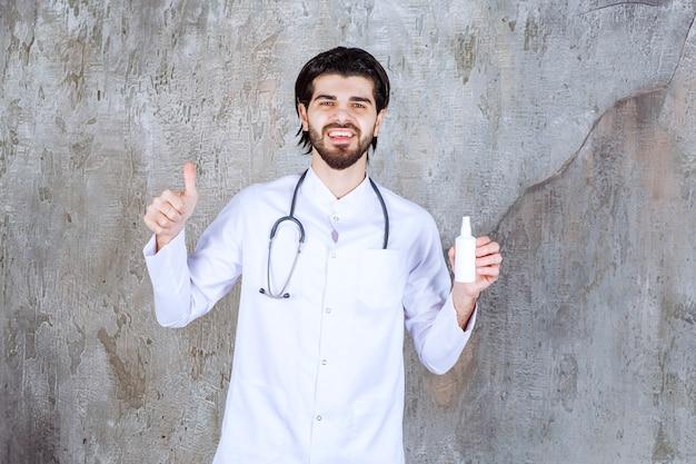 Medico con uno stetoscopio che tiene un tubo bianco di spray disinfettante per le mani e mostra il segno del pollice in su