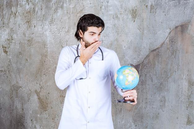 Medico con uno stetoscopio che tiene un globo del mondo e sembra confuso e pensieroso.