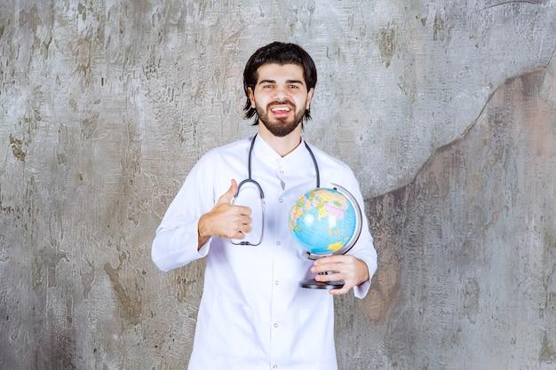 Dottore con uno stetoscopio che tiene in mano un globo mondiale e mostra un segno di successo con la mano che significa servizio in tutto il mondo
