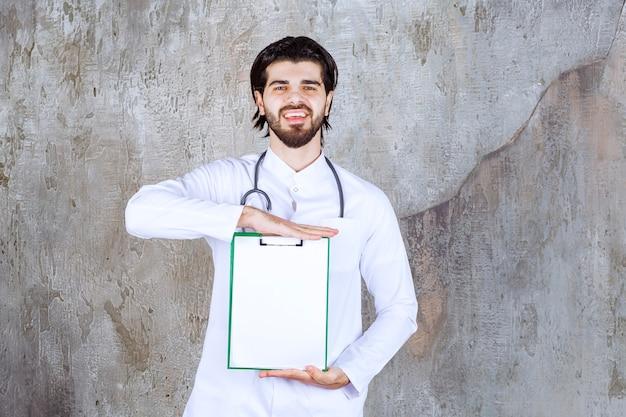 Medico con uno stetoscopio che presenta la storia di un paziente e si sente positivo