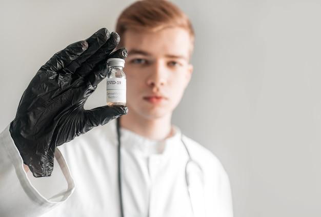 Medico con uno stetoscopio sulla spalla che tiene il vaccino covid-19