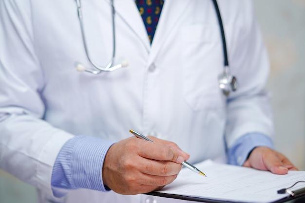 Il medico con lo stetoscopio scrive negli appunti per la diagnosi della nota dei pazienti.