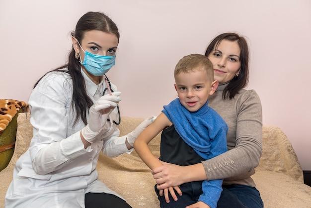 Dottore con siringa e ragazzo seduto sulle ginocchia della madre