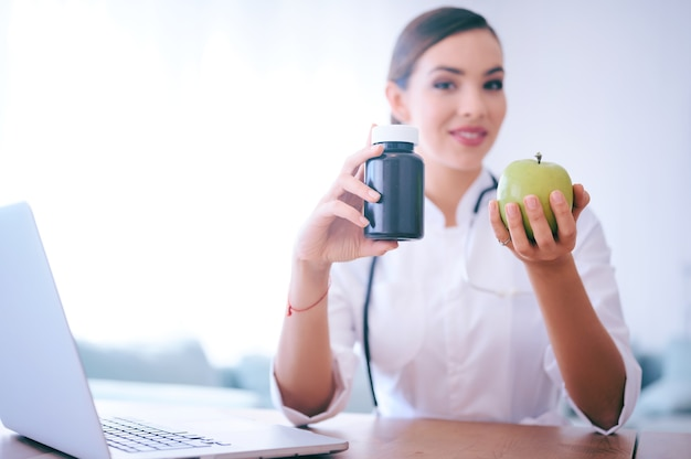 Medico donna consigliando mela invece di pillole. cibo salutare