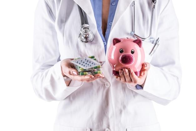 Medico donna mani pillole e salvadanaio isolato su bianco.