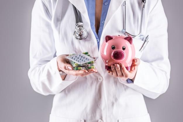 Mani della donna del medico che tengono pillole e salvadanaio.