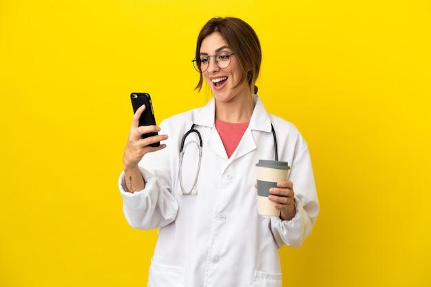 Donna medico isolata su sfondo giallo che tiene caffè da portare via e un cellulare