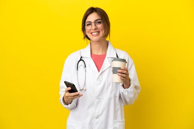 Donna medico isolata su sfondo giallo che tiene il caffè da portare via e un cellulare