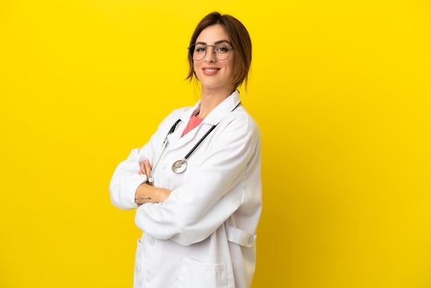 Donna medico isolata su sfondo giallo con le braccia incrociate e guardando avanti