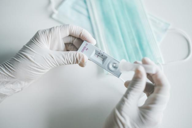 Donna medico che mostra il risultato di un kit di test rapido dell'antigene per l'autotest del covid-19 a casa