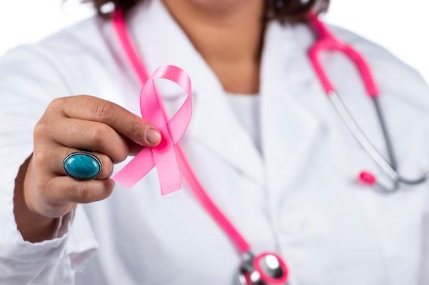 Medico donna con stetoscopio rosa che tiene il cancro al seno nastro rosa su sfondo bianco.