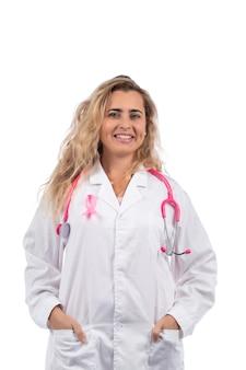 Medico donna con stetoscopio rosa con nastro rosa cancro al seno su un bianco.