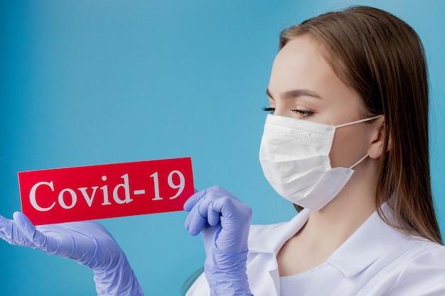 Aggiusti la donna con la maschera chirurgica che indica la carta rossa con il coronavirus del mesaage su fondo blu. organizzazione mondiale della sanità oms ha introdotto un nuovo nome ufficiale per la malattia di coronavirus chiamato covid-19