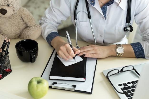 Medico che lavora in ospedale scrivendo una prescrizione, assistenza sanitaria e concetto medico