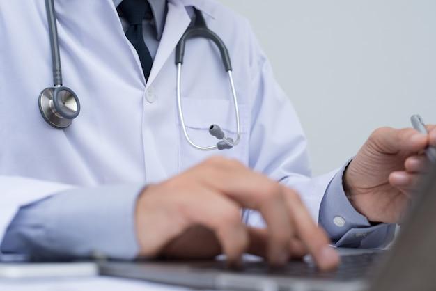 Medico che lavora al computer portatile in ufficio medico