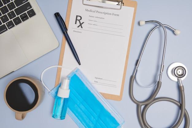 Medico sul posto di lavoro. stetoscopio medico, laptop, appunti in bianco e penna su superficie azzurra. coronavirus (covid-19. stetoscopio, occhiali da vista e maschera facciale. vista dall'alto, piatto laico, copia dello spazio.