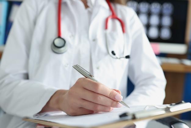 Medico che scrive in documenti medici sulla lavagna per appunti in primo piano della clinica