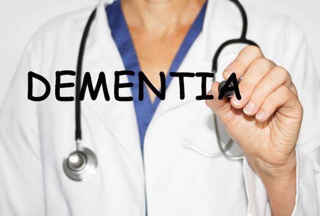 Medico che scrive parola demenza con pennarello, concetto medico