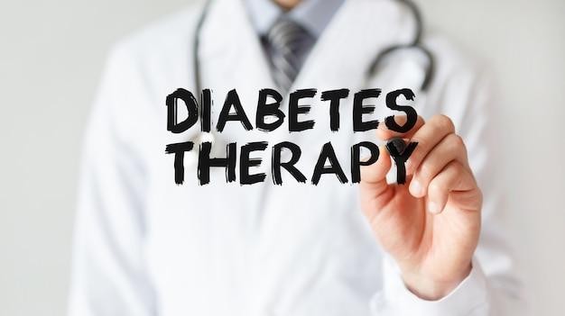 Medico che scrive la parola terapia del diabete con pennarello, concetto medico
