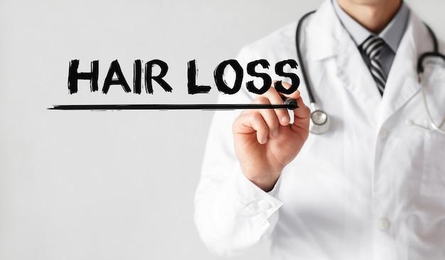 Medico che scrive parola perdita di capelli con pennarello, concetto medico