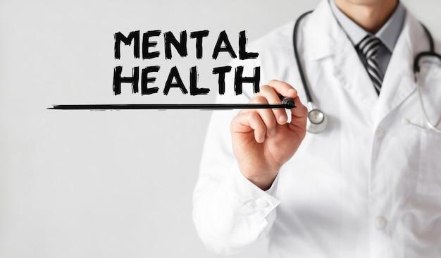 Medico che scrive parola salute mentale con pennarello, concetto medico