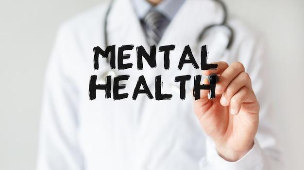 Medico che scrive la parola salute mentale con un pennarello
