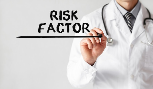 Medico che scrive parola fattore di rischio con pennarello, concetto medico