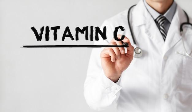 Medico che scrive parola vitamina c con pennarello, concetto medico