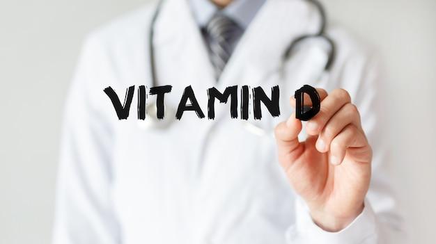 Medico che scrive parola vitamina d con pennarello, concetto medico