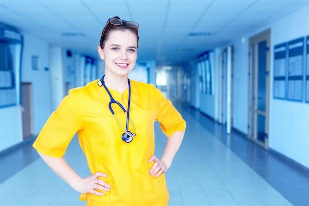 Dottore in uniforme gialla in ospedale. concetto di una bella ragazza medico felice con un sorriso.