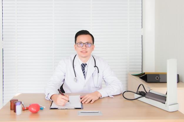 Medici, uomini asiatici, thailandesi indossano camicie da dottore e stetoscopio medico. stava prendendo appunti nell'aula d'esame.