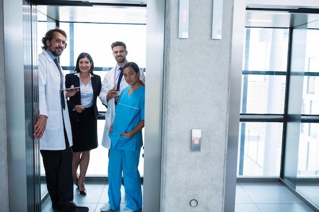 Medici e imprenditrice in piedi in ascensore
