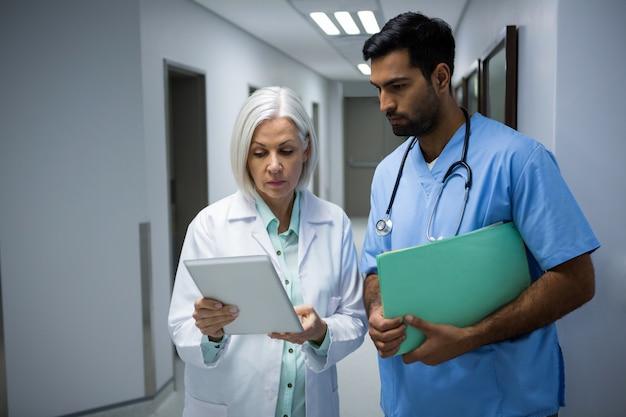 Medici che discutono sulla tavoletta digitale in corridoio