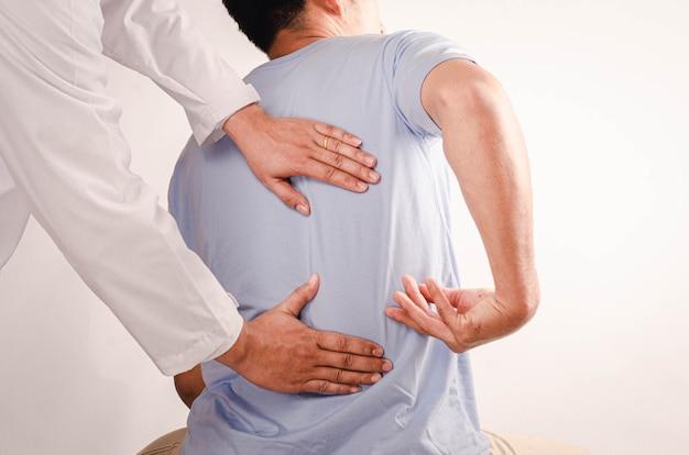 Medici che eseguono terapia fisica per giovani uomini e consigliano pazienti con problemi alla schiena.