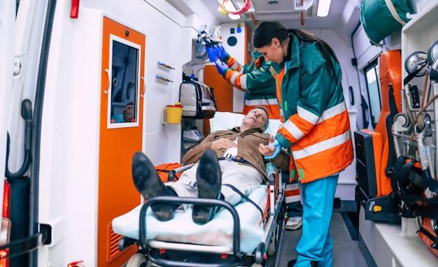 Medici di emergenza o paramedici stanno lavorando con un paziente anziano mentre giace su una barella in un'ambulanza.
