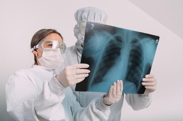 I medici esaminano i raggi x per la polmonite di un paziente covid-19 nella clinica. concetto di coronavirus.