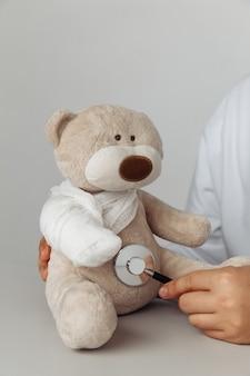 Mano di medici con stetoscopio e orsacchiotto in studio medico