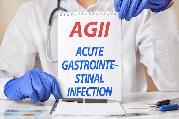 Mani di medici in guanti blu che tengono un foglio di carta con testo agii.