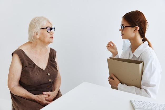 I medici nell'ufficio medico conversano con l'assistenza sanitaria del paziente