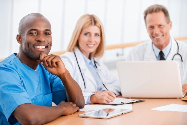 Incontro medici. tre medici allegri seduti insieme al tavolo e sorridenti alla telecamera