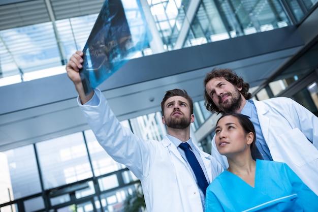 Medici e infermiere che esaminano il rapporto dei raggi x