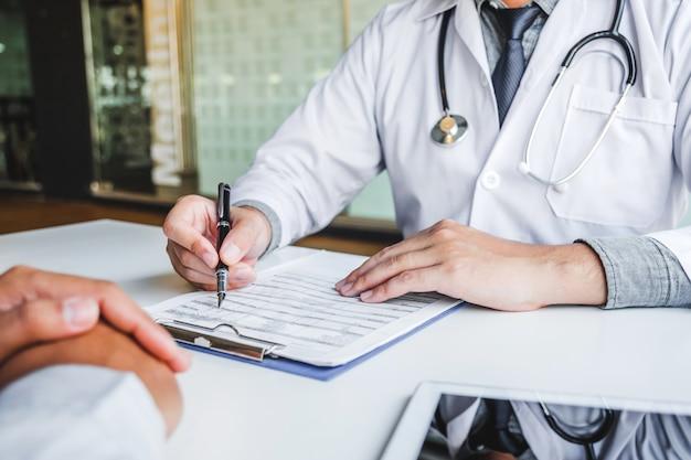 Medici e pazienti che si consultano e che esaminano la diagnostica siedono e parlano. al tavolo vicino alla finestra nel concetto di medicina dell'ospedale